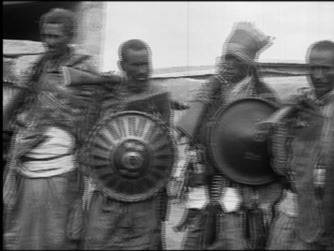 b/w 1930 pan line of black soldiers holding rifles + shields / abyssinia (now ethiopia) - anno 1930 video stock e b–roll