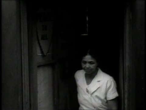 stockvideo's en b-roll-footage met 1938 ws line of black women dressed in white coming out of door and closing it behind them, sign on door, 'we thank you father,' and in heart-shape, 'peace to all.' / new york city, new york, united states - 1938