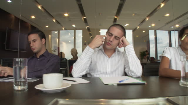 ms ds line of bored office workers sitting at meeting table / bangkok, thailand - boredom stock videos & royalty-free footage