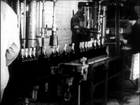 b/w 1933 line of bottles of liquor/beer on conveyor workers in distillery / repeal of prohibition - anno 1933 video stock e b–roll