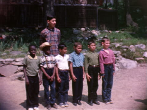 1964 line of boys standing still with teen camp counselor standing behind them / home movie - summer camp helper stock videos & royalty-free footage