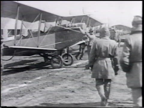 line of cadets singles walking saluting vs cadets pilots to curtiss jn4 'jenny' training biplane getting into aircraft into helmet goggles vs three... - pilot stock videos & royalty-free footage