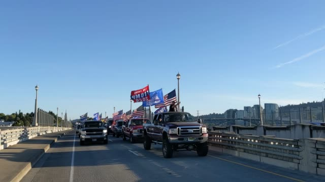 line of cars driven by pro-trump supporters with flags waving from them drive into downtown during a rally in support of the president on august 29,... - portland oregon stock videos & royalty-free footage