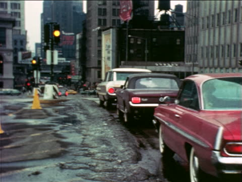 1965 line of cars in traffic stopping at red light on city street / some snow on ground / edu. - ford mustang stock videos and b-roll footage