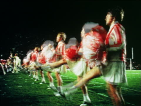 1966 line of cheerleaders in uniforms with pom poms jumping + cheering at orange bowl / florida - cheerleader stock videos & royalty-free footage
