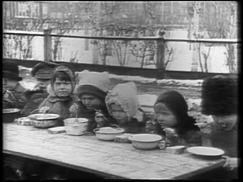 b/w 1921 line of children at table eating from bowls outdoors in winter / russia / newsreel - 1921 stock videos & royalty-free footage