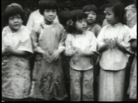 1932 montage line of children clapping at a dragon dance performance / china  - 1932 stock videos & royalty-free footage