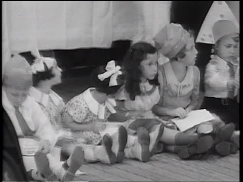 b/w 1934 line of children sitting on floor / adult legs in background / cruise ship - 1934 stock videos & royalty-free footage