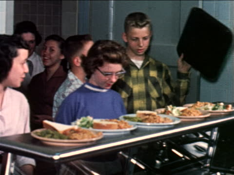 1960 line of children taking dishes of food from counter in school cafeteria / industrial - canteen stock videos & royalty-free footage