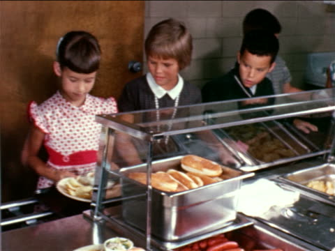 1964 line of children taking dishes of hot dogs + potato chips from woman in school cafeteria - kantine stock-videos und b-roll-filmmaterial