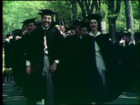 vídeos de stock, filmes e b-roll de line of college students in cap and gowns walk toward camera / outdoor graduation / university of missouri - formatura