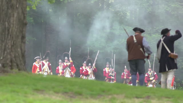 a line of colonial soldiers face off against a line red coats during a reenactment of a revolutionary war battle. - battle stock-videos und b-roll-filmmaterial