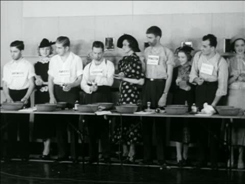 stockvideo's en b-roll-footage met b/w 1936 line of couples standing at table for shaving contest / newsreel - zij aan zij