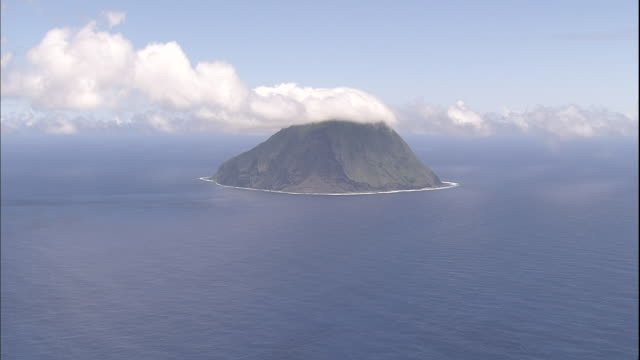 a line of cumulus clouds floats over the pacific ocean and kita iwo jima island. - iwo jima island stock videos & royalty-free footage