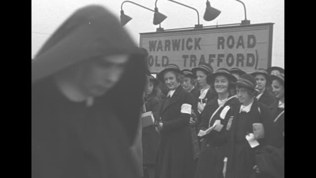 line of double decker buses approaches filled with children evacuated from london in early days of world war ii / policemen help children off bus /... - nun stock videos and b-roll footage