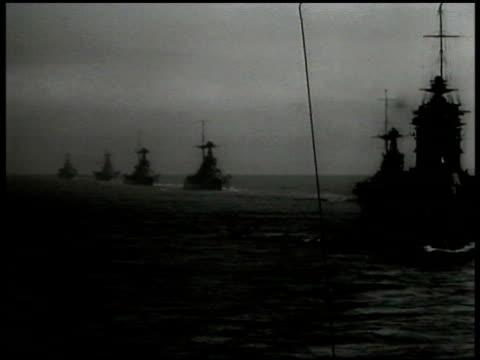 vídeos de stock e filmes b-roll de line of english royal navy battleships at sea ms cannon barrels on deck ms destroyer ship at sea - 1935