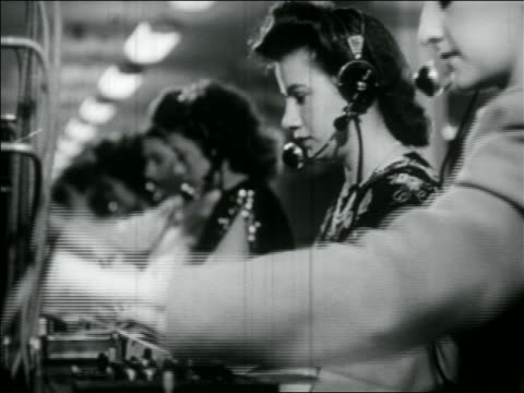 b/w 1950 line of female telephone operators in headphones working at switchboards - customer service representative stock videos & royalty-free footage