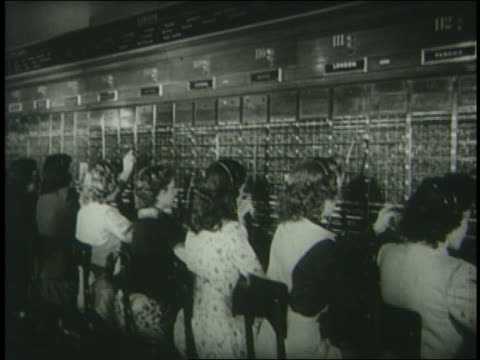 b/w 1950 rear view line of female telephone operators sitting at switchboard / newsreel - 電話交換機点の映像素材/bロール
