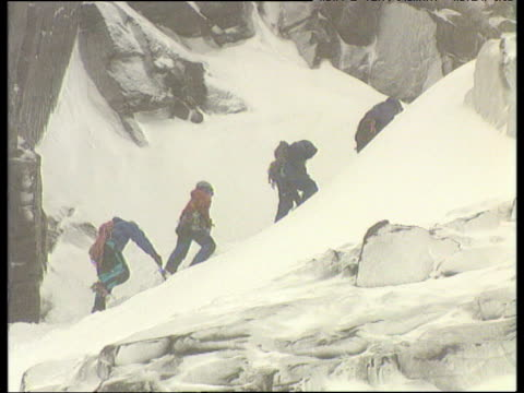 line of four mountaineers trailing up side of very snowy mountain; zoom out to whole mountain in snowstorm with tiny mountaineers - bbc archive stock-videos und b-roll-filmmaterial