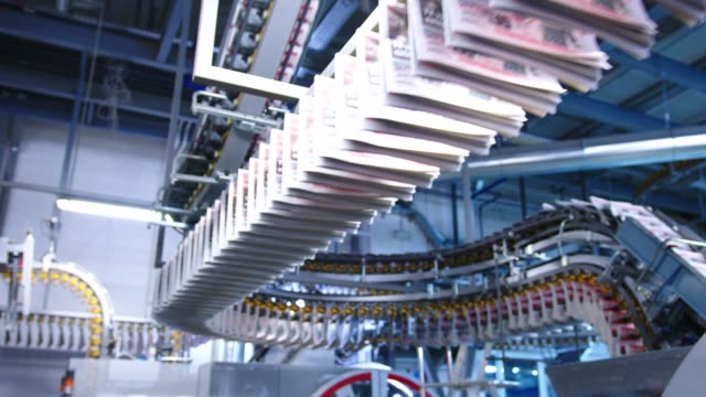 a line of freshly printed newspaper hanging of a moving conveyor belt - printing press stock videos & royalty-free footage