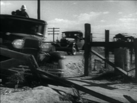 vidéos et rushes de b/w 1936 line of fully loaded cars pulling into driveway of migrant worker camp - 1936