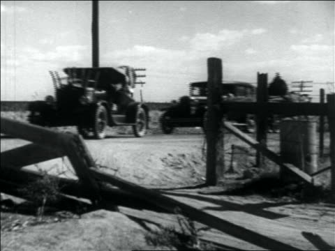 vidéos et rushes de b/w 1936 line of fully loaded cars turning into driveway of migrant workers camp - 1936