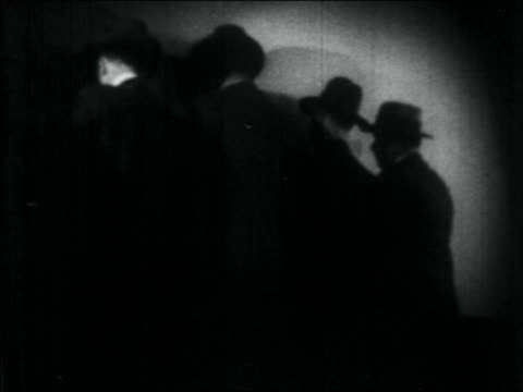 B/W 1934 REAR VIEW line of gangsters up against wall / close up shadow of man's hand pointing pistol