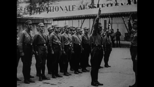 line of german military personnel possibly brown shirts looks on as one man steps forward issues nazi salute to superior turns smartly and walks back... - braun stock-videos und b-roll-filmmaterial