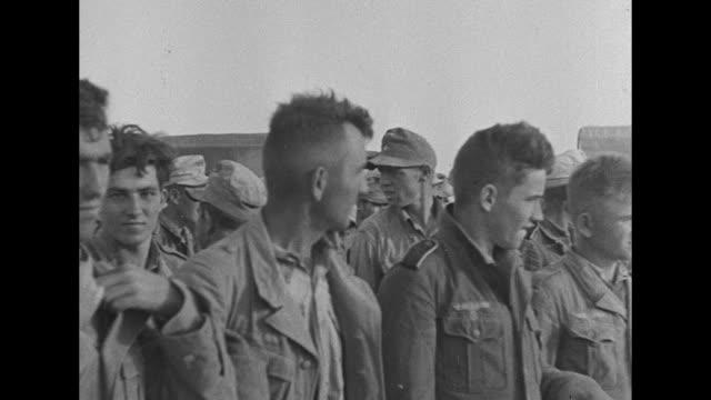 line of german prisoners walking along road / two shots of prisoner being interrogated by british officers / two shots of large group of prisoners... - deutsches militär stock-videos und b-roll-filmmaterial
