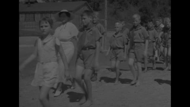line of girls wearing white ruffled tops and white shorts approaches and passes camera from the right; camp barracks-type building stands in... - summer camp stock videos & royalty-free footage