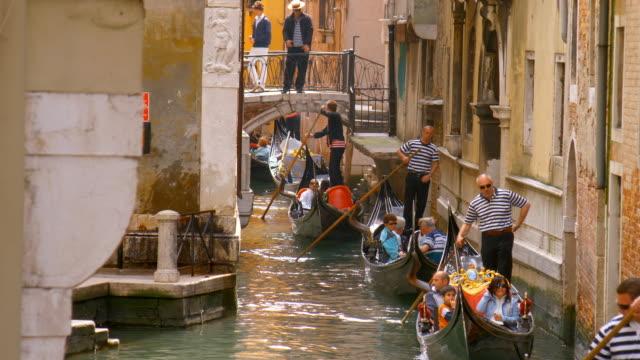 a line of gondolas move down the narrow waterway of rio di san salvador in venice, italy. - kanal bildbanksvideor och videomaterial från bakom kulisserna