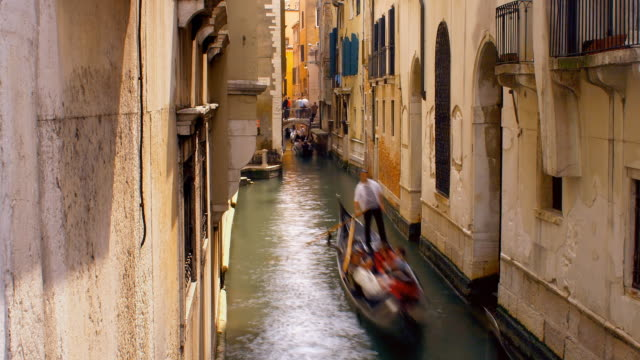 vídeos de stock e filmes b-roll de a line of gondolas move down the narrow waterway of rio di san salvador in venice, italy. - embarcação comercial