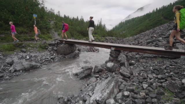 linie der wanderer überquert holzbrücke stream in bergen - beweglichkeit stock-videos und b-roll-filmmaterial