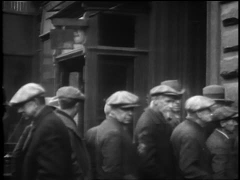 pan line of homeless men waiting to be fed / great depression / newsreel - soup kitchen stock videos & royalty-free footage