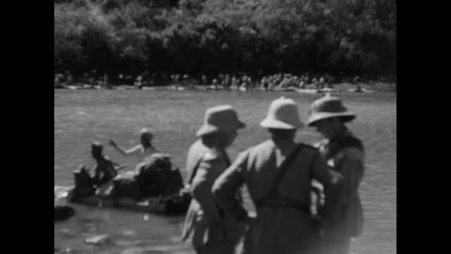 VS line of Italian and Ethiopian men trudge though river with pack animal / VS turbaned natives poling Italians in reed boats / pan around riverbank...