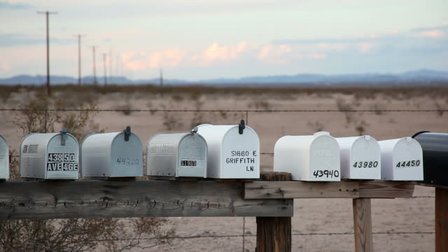 ms cu line of mailboxes in front of a desert landscape / indio, california, usa - letterbox stock videos & royalty-free footage