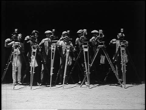B/W 1922 line of men hand cranking movie cameras outdoors / Hollywood