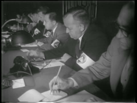 vídeos y material grabado en eventos de stock de b/w 1951 line of men in armbands write on pads of paper at table in civil defense control / newsreel - 1951