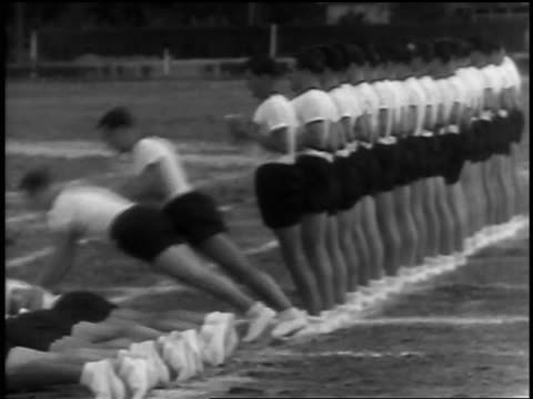 b/w 1933 line of men in identical shorts + t-shirts falling to ground one after another - conformity stock videos & royalty-free footage
