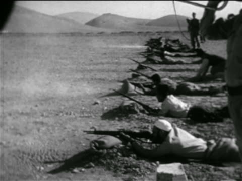 line of men lying on ground shooting rifles in practice / syria / newsreel - 1957 stock-videos und b-roll-filmmaterial