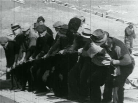 b/w 1934 line of men pulling rope on hill in wpa construction project / documentary - new deal video stock e b–roll