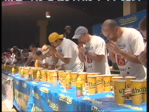 line of men shove food into their mouths during a hot dog eating contest. - contestant stock videos & royalty-free footage