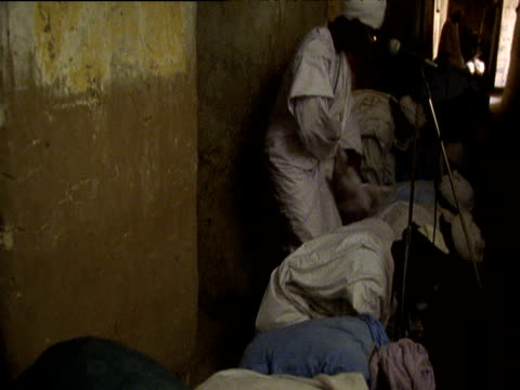 stockvideo's en b-roll-footage met line of men wearing white robes and hats kneel down to pray in mosque timbuktu - kleding