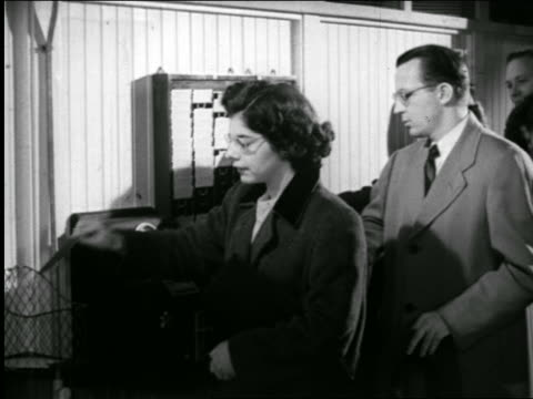 b/w 1947 line of men + women punching into time clock / industrial - punching stock videos and b-roll footage