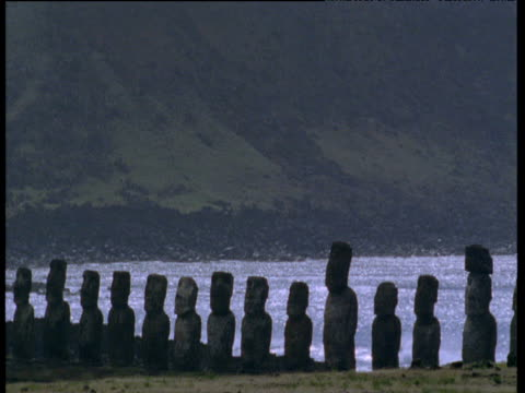 line of moai monolithic statues in front of sea - polynesian culture stock videos & royalty-free footage