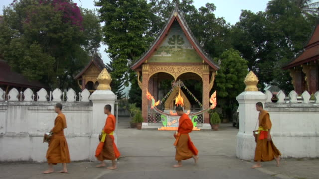 ws line of monks passing temple / luang prabang, laos - religion stock videos & royalty-free footage