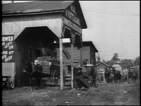 B/W 1920 line of mules + wagons delivering cotton to mill / Southern US / documentary