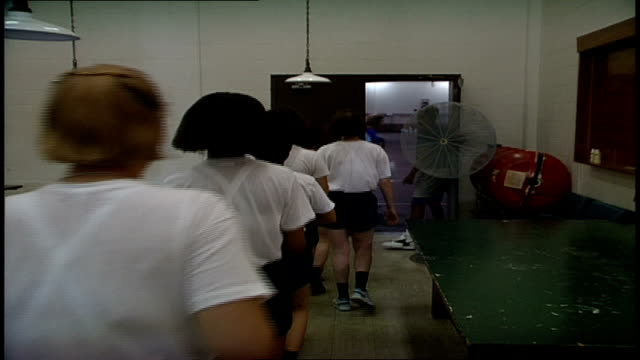 line of navy rotc recruits walking paast camera in white tees in orlando, florida - allarme di prova video stock e b–roll