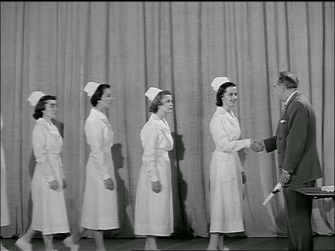 stockvideo's en b-roll-footage met b/w 1954 line of nurses in uniform receiving diplomas + handshake in ceremony - slagen school