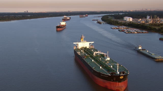A line of oil tankers move slowly down a Louisiana river.